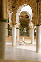 Senegal, Touba.  Worshipper Carrying Shoes Walking through Prayer Halls for Overflow Crowds at the Grand Mosque.