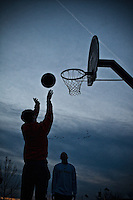 """Students from Otterbein College gather on the basketball courts at Alum Creek park South for several games of """"Horse"""" as the sun sets across the creek."""