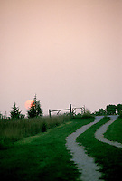 Old farm road at sunset- cattle trail and truck tracks head towards gate and setting sun