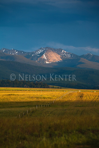 The sun shines a spot light on a mountain peak in the Anaconda Pintler Range