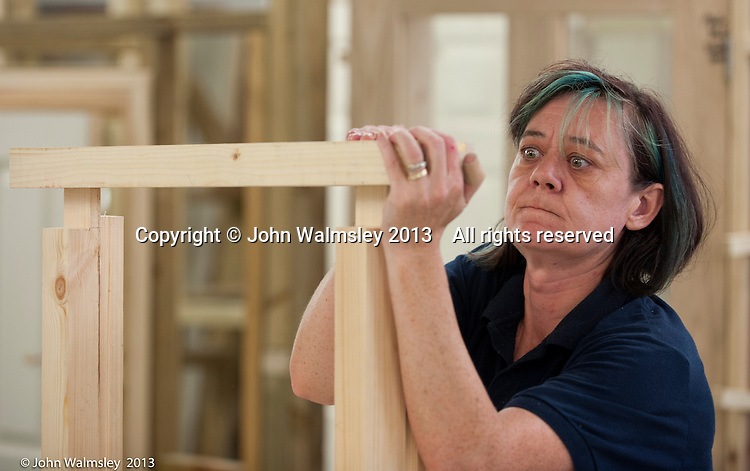 Woman fitting together the sash window frame she's making.  Carpentry and joinery training, Able Skills, Dartford, Kent.