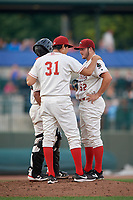 Great Lakes Loons pitching coach Luis Meza (31) talks with pitcher Zach Willeman (52) and catcher Jair Camargo (21) during a Midwest League game against the Clinton LumberKings on July 19, 2019 at Dow Diamond in Midland, Michigan.  Clinton defeated Great Lakes 3-2.  (Mike Janes/Four Seam Images)