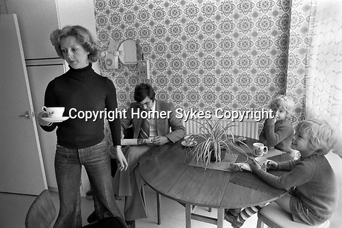 1970s England, a middle income professional couple at home with their two children. In the kitchen, mother making afternoon tea, sandwiches for the two boys, and a cup of tea for her husband who is reading the newspaper and paying no attention at all or interest in his children. He is bored family life. 1977 New town modern housing development  Milton Keynes Buckinghamshire.