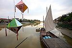 Old-fashioned Japanese lanterns hang from a bridge near a boat anchored in the river one late afternoon in Hoi An, Vietnam. April 22, 2012.
