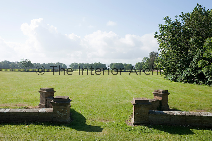 Sections of the garden are punctuated by low stone walls opening onto swathes of mown lawns and the park beyond