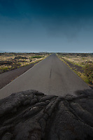 Amazing view of the edge of the road buried in lava rock from the eruption of Kilauea, under a stormy sky, on the Hawaii Big Island
