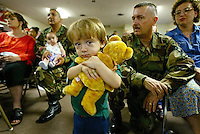 Nicholas Jones, 2, cluthches a bear given to him by the American Red Cross, as his mom and dad, at right, Staff Sgt. Eugene Jones, and Kathy Jones, of Ocala, listen to speakers at a family informational meeting before his deployment Wednesday night, March 12, 2003. The meeting gives families valuable information about wherre their soldier will be to what kinds of things the remaining family members can expect to deal with while their loved one is deployed in service during the possible war with Iraq.(Kelly Jordan)