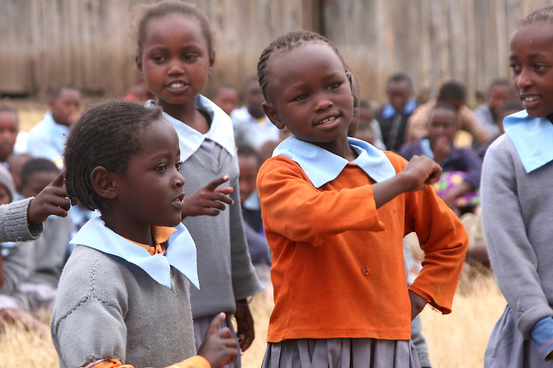 """In Matanya, a small rural village near the base of Mount Kenya, primary school students gather in the only auditorium they know - the bare earthen floor - where they perform a poem encouraging academic discipline.  """"Never give up,"""" is the message and """"work hard.""""  Many of these students are orphaned and most are extremely poor."""