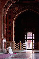 Agra, India.  Taj Mahal Interior.  Man Reading the Koran while awaiting prayer time.