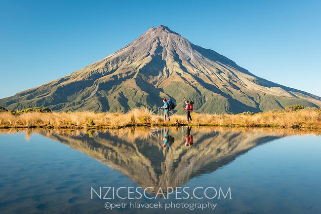 Hikers under Taranaki, Mt. Egmont with reflections in alpine tarn, Egmont National Park, North Island, New Zealand, NZ