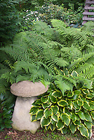 Garden ornament mushroom with hosta and ferns in shade