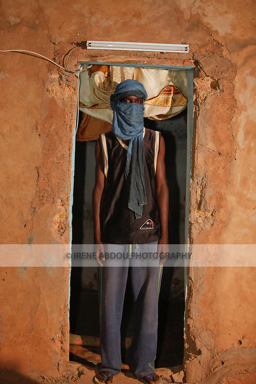 A young Fulani man in a turban stands in the doorframe of his home in Djibo, northern Burkina Faso.