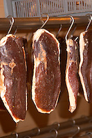 Duck's breast (magret or filet de canard) hanging on hooks in a temperature controlled room to make dried duck's breast. Ferme de Biorne duck and fowl farm Dordogne France Workshop on how to make foie gras duck liver pate and other conserves