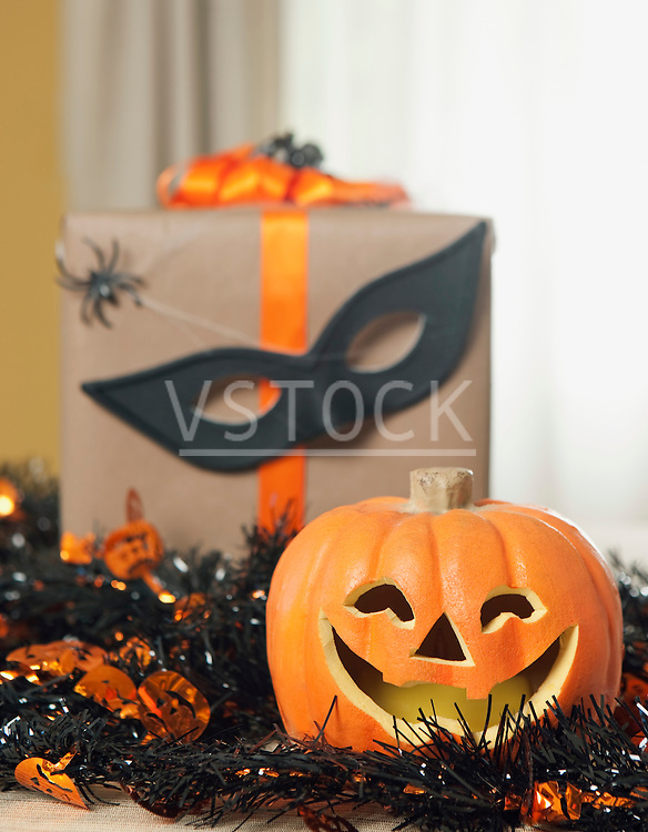 USA, California, La Quinta, Jack o' lantern and garland, Halloween gift with spiders and mask in background