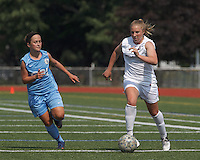 Boston Aztec forward Corey Persson (17) on the attack as Seacoast United Mariners midfielder Krista Hagen (14) closes. In a Women's Premier Soccer League (WPSL) match, Boston Aztec (white) defeated Seacoast United Mariners (blue), 2-1, at North Reading High School Stadium on Arthur J. Kenney Athletic Field on on June 23, 2013. Due to injuries through the season, Seacoast United Mariners could only field 10 players.