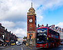 A number 91 bus to Trafalgar  Square passes the Clock Tower, on Crouch End Broadway, during lockdown.