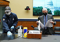 A worker wipes down the desk where Director of the National Institute for Allergy and Infectious Diseases Dr. Anthony Fauci will testify before the House Committee on Energy and Commerce on the Trump Administration's Response to the COVID-19 Pandemic, on Capitol Hill in Washington, DC on Tuesday, June 23, 2020.   <br /> Credit: Kevin Dietsch / Pool via CNP/AdMedia