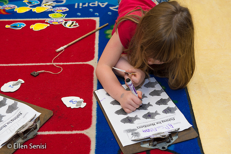 "MR / Schenectady, NY. Zoller Elementary School (urban public school). Kindergarten inclusion classroom. Student (girl, 6) writes down a number as she plays ""go fish"" game at math learning center time.  MR: Bin1. ID: AM-gKw. © Ellen B. Senisi."