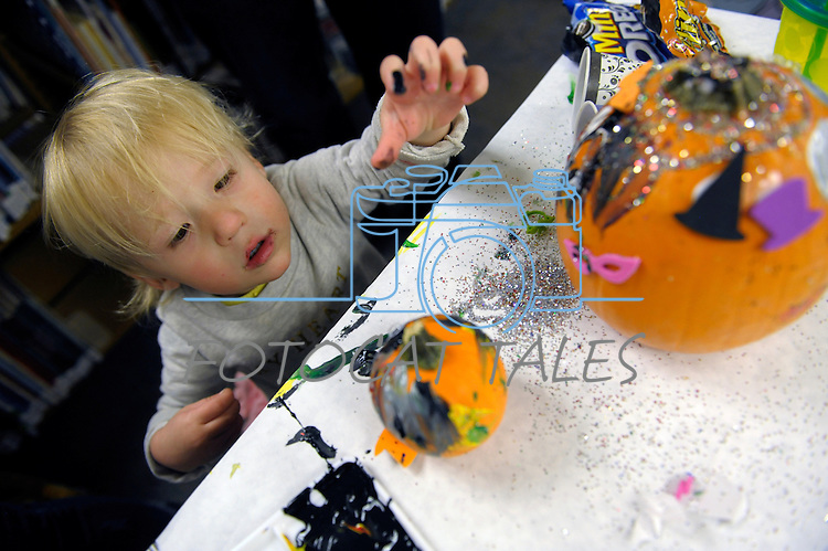 Addie Cox, 22 months, reaches for some paint while creating some Halloween art at the Carson City Library Monday, Oct. 27, 2014. As part of the library's Halloween festivities, dozens of children decorated pumpkins or gourds and took part in a costume contest.