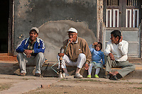 Nepal, Patan.  Men Relaxing on Sidewalk, one Smoking Water Pipe.