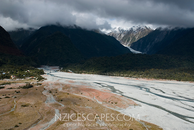 Looking into a clouded valley across Waiho River with Franz Josef Glacier lurking right of centre - Westland National Park, West Coast