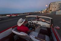 Man in vintage car driving along Malecon road at night, Havana, Cuba