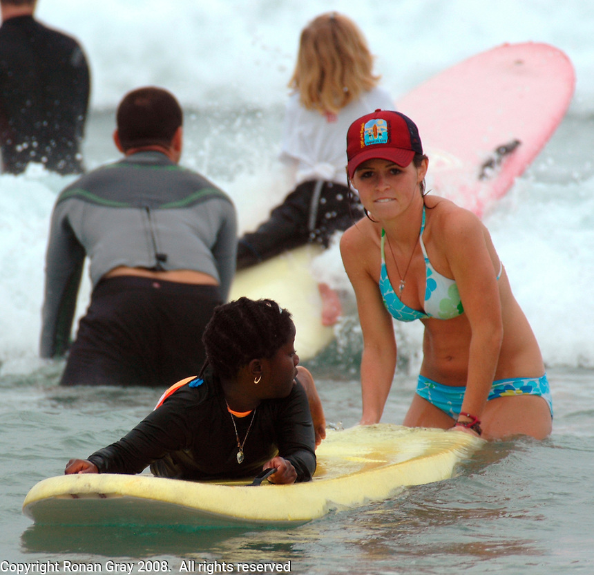 """Saturday, August 23 2008.  Maddie Rupp helps """"Chare"""" (no last name given) into a wave while fellow volunteer Jeff Lhuillier (background) heads out through the surf with his daughter Emma (6) during the 22nd Annual Kids Day hosted by the Windansea Surf Club at La Jolla Shores.  Lhuillier, a French native who usually does the cooking at the annual event, took a break to give his daughter a quick surf lesson."""