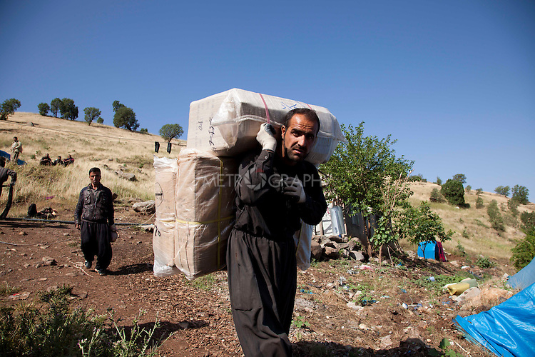 SHABADEEN, IRAQ: A smuggler heads towards the border with goods strapped to his back...Thousands of Kurdish smugglers make a living ferrying goods between Iraq and Iran. They smuggle everything from clothes, to make-up, to alcohol which is forbidden in Iran. The smugglers make around 100,000 Iranian Rials ($8 USD) per journey and make 3 journeys per day...Photo by Aram Karim