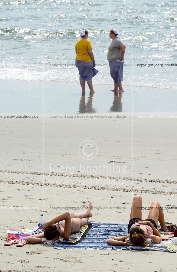 USA, New Jersey, Ocean City, Amish People, two amish women dressed with clothes at the beach, in contrast two other young women in Bikini / Amische, Amischen sind eine täuferisch-protestantische Glaubensgemeinschaft