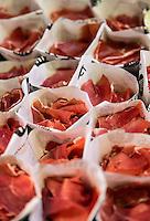 Dried ham snacks for sale by vendor in La Boqueria market, Barcelona, Spain