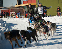Musher Ray Reddington Jr. maneuvers his team down city streets at the ceremonial start of the 2014 Iditarod Dogsled Race in downtown Anchorage, Alaska. Sixty-nine mushers paraded their teams through Anchorage today and will depart from the official start in Willow tomorrow to begin the 975-mile race to Nome.