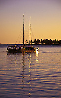 Hawaiian sailing canoe off the coast of Ala Moana beach park, island of Oahu at sunset