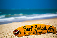 Yellow surfboard sign for a surf school, on the famous, beautiful Porto de Galinhas beach, with blurred Atlantic Ocean waves, in Pernambuco, Brazil