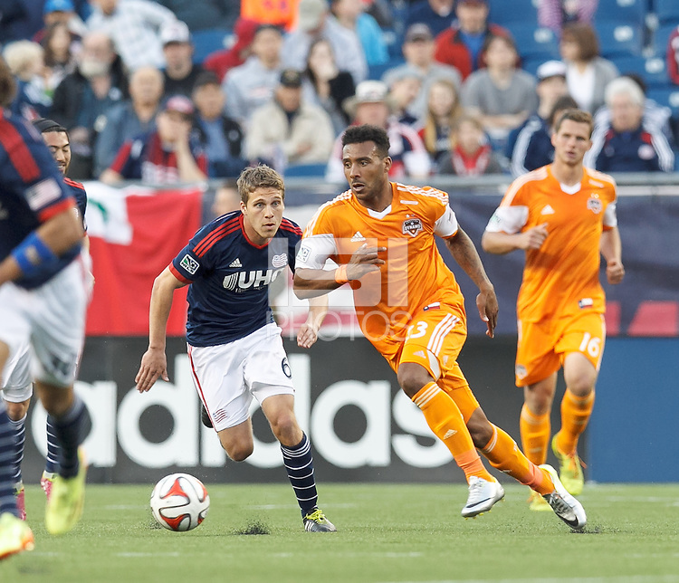 Houston Dynamo forward Giles Barnes (23) works to clear ball as New England Revolution substitute midfielder Scott Caldwell (6) closes. In a Major League Soccer (MLS) match, the New England Revolution (blue/white) defeated Houston Dynamo (orange), 2-0, at Gillette Stadium on April 12, 2014.