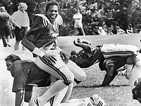 Argos' slotback, Mike Harris, relaxes during calisthenics at Canadian Football League training camp in Guelph. His 'cushion' is Carlos Henderson. Harris came to Argos as free agent from Hamilton Tiger-Cats. He says he'd prefer to play defensive position.