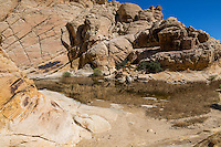 Red Rock Canyon, Nevada.  Calico Tanks at end of Trail.  Sandstone Shows Cross-bedding from ancient Sand Dunes.  Desert Varnish appears on rocks on left in foreground and background.
