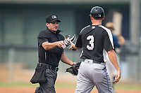 Home plate umpire John Perez hands batting gear to Grand Junction Rockies manager Jake Opitz (3) during a Pioneer League game against the Helena Brewers at Kindrick Legion Field on August 19, 2018 in Helena, Montana. The Grand Junction Rockies defeated the Helena Brewers by a score of 6-1. (Zachary Lucy/Four Seam Images)