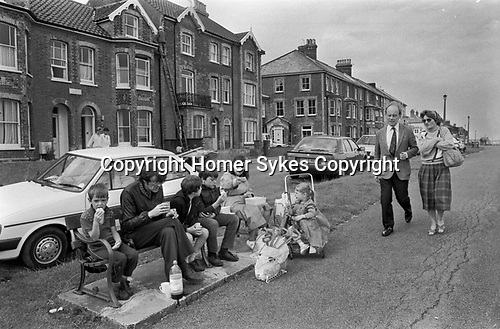 Family 1980s UK. Children and parents eating a picnic lunch sitting on a street bench Southwold, Suffolk, East Angelia, 1985