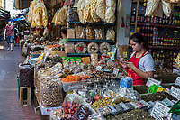 Bangkok, Thailand.  Young Woman Using her Cell Phone in a Shop in the Chinese Food Market, Chinatown.