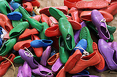 Lolgorian, Kenya. Brightly coloured plastic shoes on sale at the market