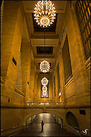 Grand Central Terminal interior with chandeliers. A lone woman was walking underneath the connecting bridge...