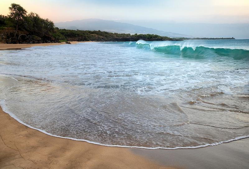 Waves and sunrise on Hapuna Beach with Hualalai volcano in background. Hawaii Island