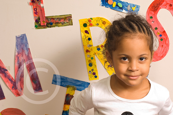 Preschool classroom New York City portrait of girl with colorful alphabet letters on wall behind her horizontal Hispanic American