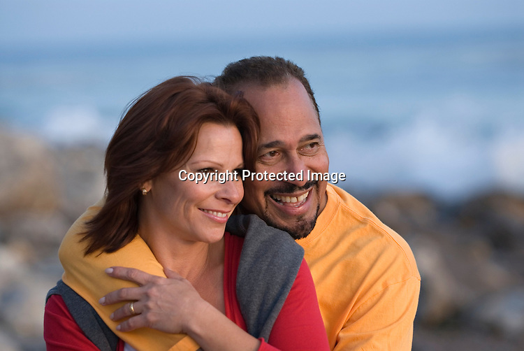 Mature couple smiling at beach