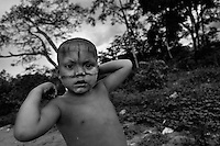 A young Nukak boy, having his face painted with the red dye, stands in front of the jungle trees in a refugee settlement close to San Jose del Guaviare, Colombia, 4 September 2009. The Nukak Maku people, nomadic hunter-gatherers from Amazonia, were violently driven out of the jungle by the Colombian guerilla and paramilitary squads. Now, roughly cut off their original tribal lifestyle, they stuck between worlds. They learn from the (mainly Christian) aid workers to use clothes, to listen to the radio, to beg for money. Although their digestion suffer, they love to eat sweets, cookies and other western food. They have hunted out all the animals around and now there is nothing left for them. Nukak can not return to the jungle, their world has already passed through an irreversible change.