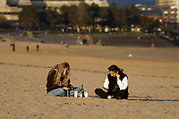 Pictured: People gather on the beach in Swansea Bay. Friday 16 April 2021<br /> Re: People enjoy an evening out after Covid-19 lockdown rules were relaxed, in Swansea Bay, Wales, UK.