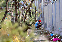 """Pictured: A migrant sneaks in through the fence to get belongings at Moria camp on Lesbos island.<br /> Re: Up to 4,000 migrants were evacuated from the Moria camp on the Greek island of Lesbos after a large fire destroyed tents and prefabricated homes.<br /> No injuries have been reported, and some migrants have now been allowed to return to the camp.<br /> Police are investigating whether the fire was deliberate, but an aid worker said it started after a food dispute.<br /> There are some 5,600 refugees currently in Lesbos, according to the UN, but the island only has capacity for 3,600.<br /> The fire destroyed 30% of the camp, according to Aris Vlashopoulos, an aid worker with the Swiss charity SAO.<br /> """"People are returning to the camp now as I can see. But the biggest number of the refugees are already on the streets, sleeping outside,"""" he added."""