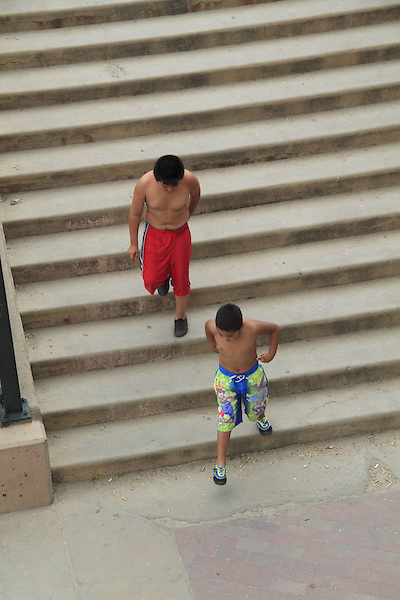 Two Hispanic boys running down the stairs in an urban park, Denver, Colorado. .  John offers private photo tours in Denver, Boulder and throughout Colorado. Year-round Colorado photo tours.