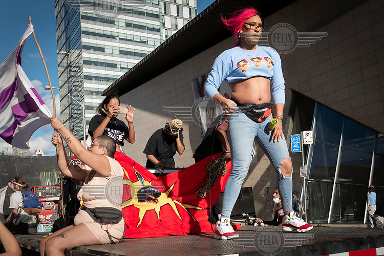 Women on a flat bed at a rally to defund and abolish the police is held by 'Not Another Black Life', a racial justice organisation.