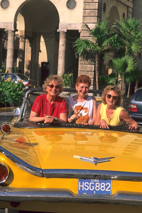 Smiling tourists in a 1950's convertible taxi.  Havana, Habana, Cuba.